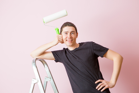 Photo of man with paint roller next to ladder 版權商用圖片
