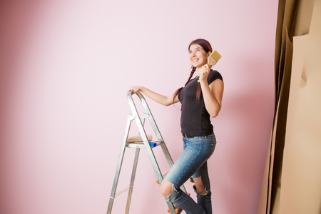 Picture of cheerful woman with brush next to stepladder and roller against blank pink wall Stock Photo