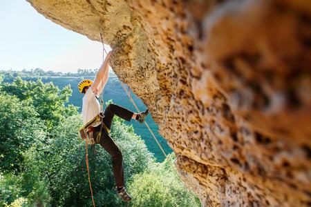 Photo of tourist man in helmet clambering over rock up