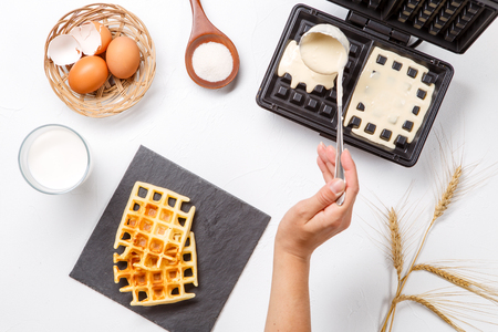 Photo on top of flour, eggs, waffle iron, spikelets, fresh roasted waffles, human hands 스톡 콘텐츠