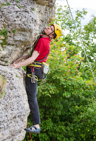 Photo of sportsman in yellow helmet clambering over rock against background of green trees