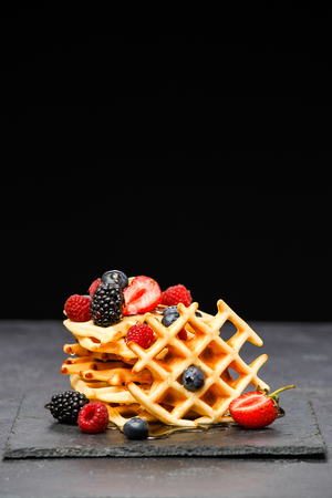 Photo of viennese wafers with berries pouring honey on black background 版權商用圖片