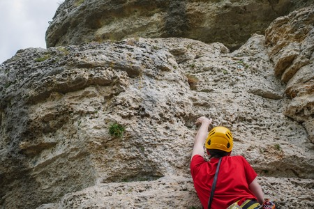 Image from back of man in helmet clambering over rock