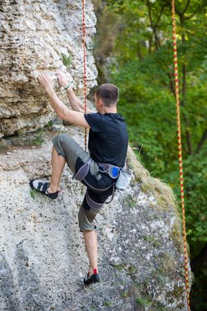 Photo of sports man climbing mountain