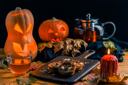 Photo of halloween pumpkins, cakes, cup of tea Stock Photo