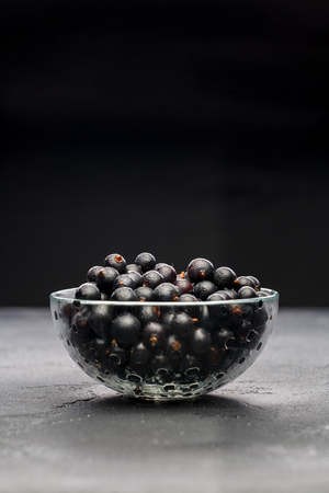 Photo of black currant in glass transparent cup Standard-Bild - 109771804