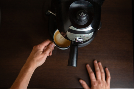 Photo of coffee maker, hands of man pouring coffee in mug