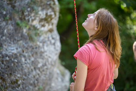 Image of young woman rock climber with safety rope in hands of rock on background of green trees