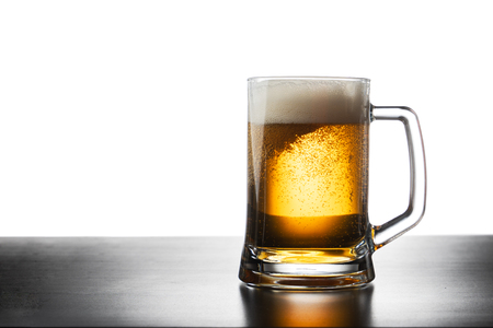 Frosty mug of light beer on black table