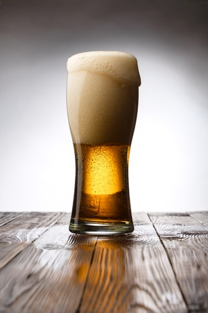Frosted glass of light beer on wood table