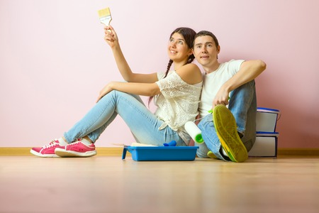Photo of young woman and man with paint roller sitting on floor 版權商用圖片