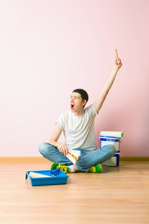 Photo of man with brush sitting on floor