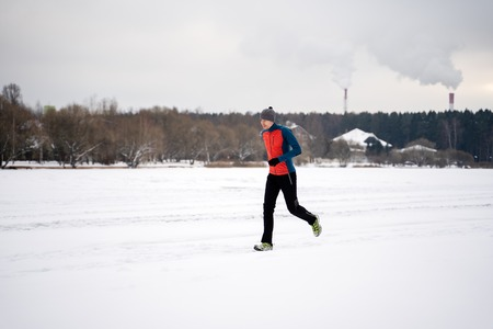 Photo of running athlete among trees in winter forest Standard-Bild