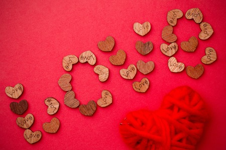 The word love is laid out from a variety of wooden hearts Foto de archivo