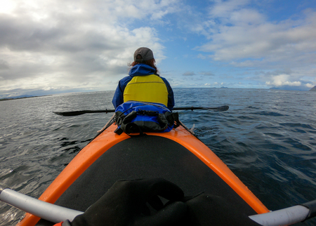 Image from back of female tourist with paddle on canoe floating