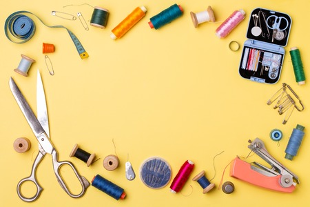 Composition with threads and sewing accessories - scissors, centimeter, pins on yellow background. 免版税图像