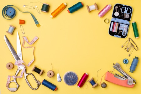 Composition with threads and sewing accessories - scissors, centimeter, pins on yellow background. Foto de archivo