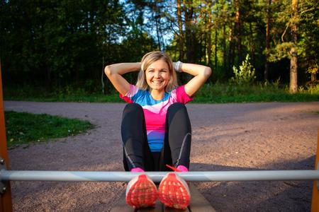 Athlete blonde with hands behind head practicing on wooden bench in park on summer. Standard-Bild - 117834544