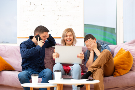 Friends sit on the couch, chatting and using a smartphone, desktop computer, laptop. Standard-Bild - 117834556