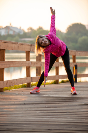 Image of young girl stretching in summer park Standard-Bild - 117834050