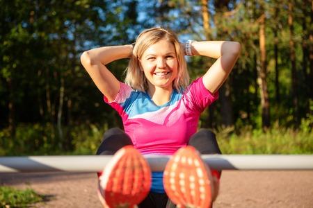 Happy blonde with hands behind head practicing on bench in park on summer. Standard-Bild - 117834052