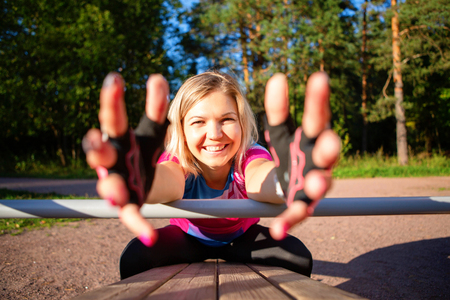 Athlete girl pulling hands forward is exercising at wooden bench in park on summer. Standard-Bild - 117834051