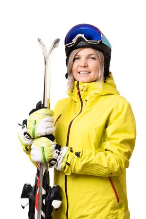 Smiling girl in helmet holding skis Standard-Bild - 117834060