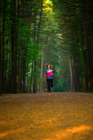 Photo from back of sports woman running through park among trees on summer. Standard-Bild - 117834062
