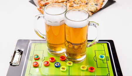 Photo of two mugs of frothy beer, table football Standard-Bild - 118056427