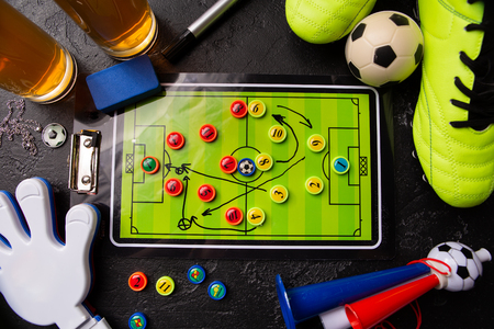 Image on top of two mugs of foam beer, table football, ball, football boots, pipe, rattle toy Standard-Bild - 118056435
