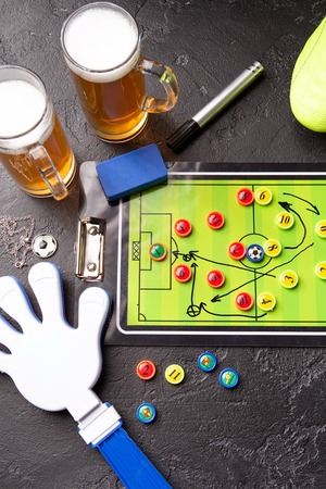 Image on top of two mugs of foam beer, table football, ball, rattle toy Standard-Bild - 118056432