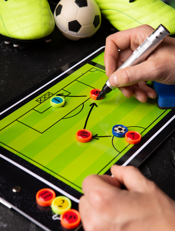 Photo of table football, soccer ball, boots, human hands with marker Standard-Bild - 118056438