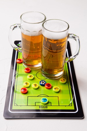 Picture of two mugs of frothy beer, table football Standard-Bild - 118056439