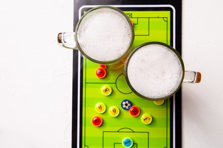Image on top of two mugs of frothy beer, table football Standard-Bild - 118056442