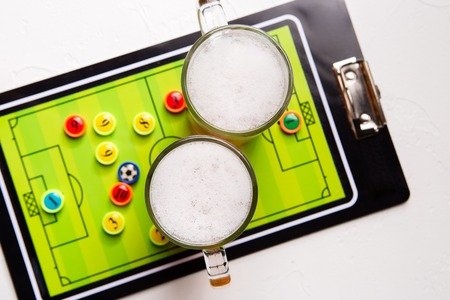 Image on top of two mugs of frothy beer, table football Standard-Bild - 118056633