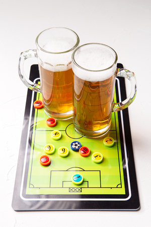 Picture of two mugs of frothy beer, table football Standard-Bild - 118056630