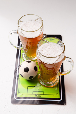 Photo on top of two mugs of frothy beer, table football, ball Standard-Bild - 118056632