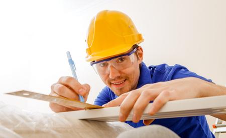Photo of joiner in helmet, goggles, with ruler, pen in his hand Standard-Bild - 118056635