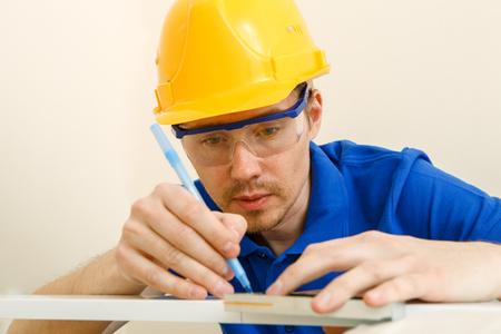 Photo of joiner in helmet, goggles, with ruler, pen in his hand Standard-Bild - 118056636