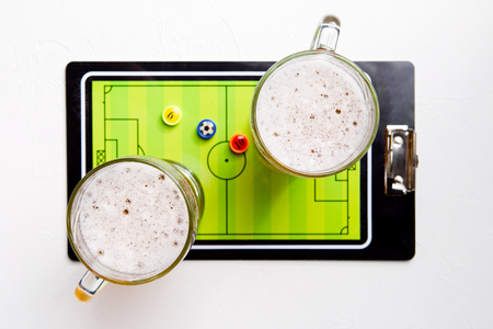 Picture on top of two mugs of frothy beer, table football Standard-Bild - 118056638