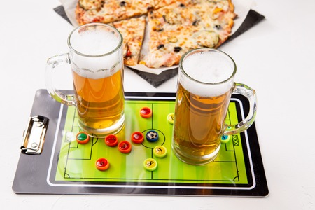Photo of two mugs of beer, table football, pizza Standard-Bild - 118056640