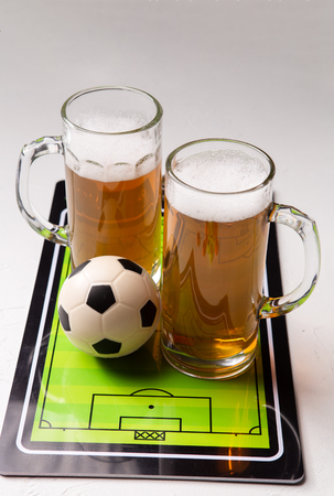 Photo on top of two mugs of frothy beer, table football, ball Standard-Bild - 118056768