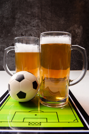 Photo on top of two mugs of frothy beer, table football, ball Standard-Bild - 118056769