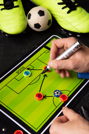 Photo of table football, soccer ball, boots, human hands with marker Standard-Bild - 118056765