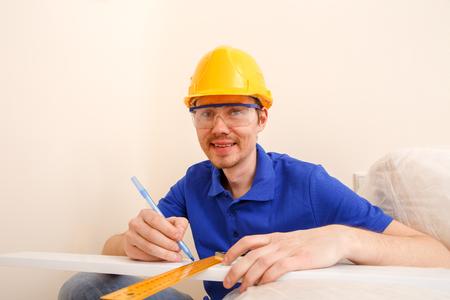 Image of joiner in helmet, goggles, with ruler, pen in his hand Standard-Bild - 118056770