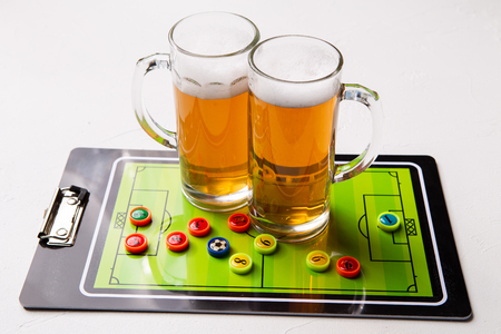 Photo of two mugs of frothy beer, table football Standard-Bild - 118056776