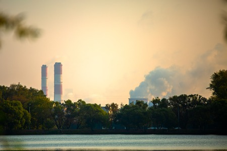 Photo of trees, river, industrial pipes with smoke. Standard-Bild - 118056775