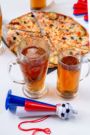 Photo of mugs with foam beer, pizza, pipes