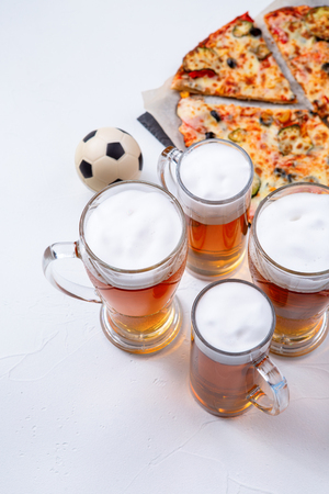 Photo from above of glasses with foam beer, pizza, pipes