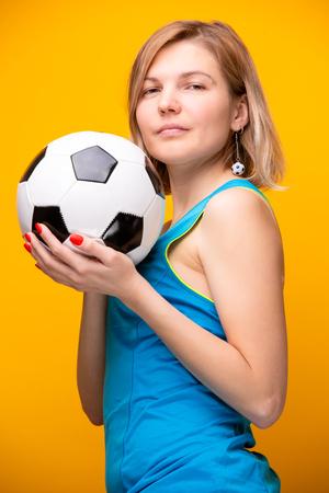 Foto von Blondine mit Fußball auf Gelb